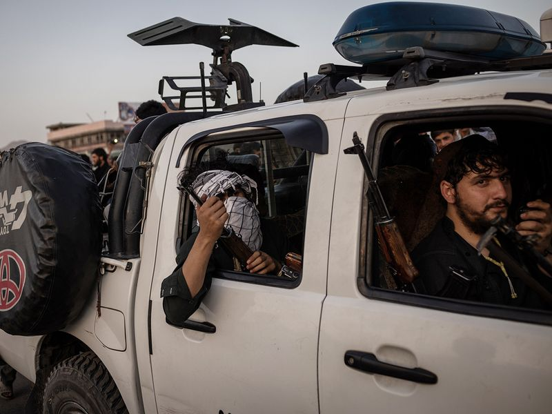 Taliban fighters drive into Kabul, on Sunday.