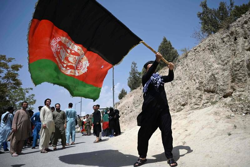 An Afghan waves the national flag protest