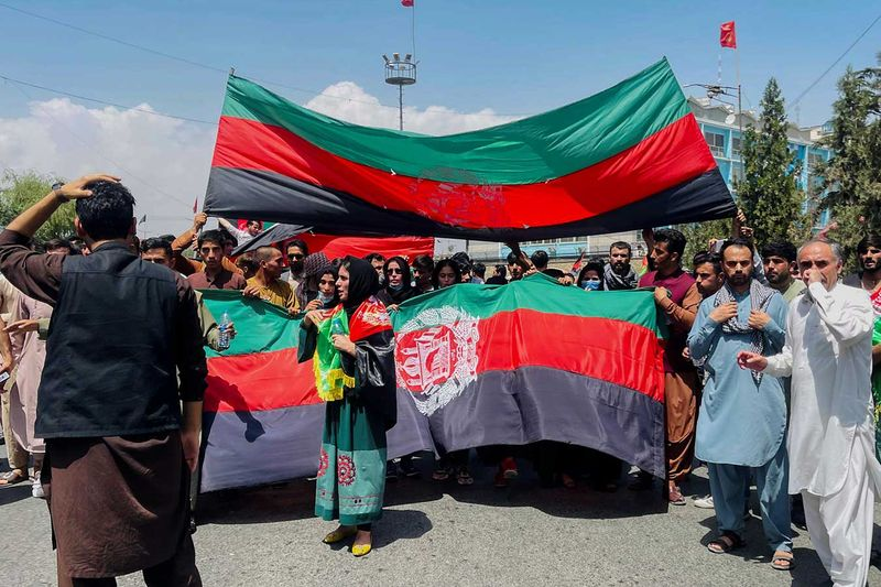 People carry the national flag at a protest