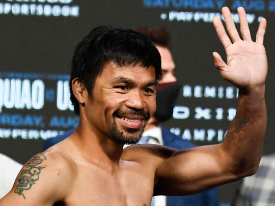 Manny Pacquiao waves after the weigh-in before his fight against WBA welterweight champion Yordenis Ugas
