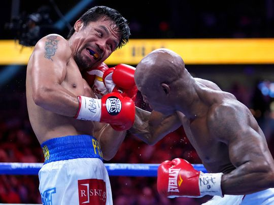 Manny Pacquiao (left) fights Yordenis Ugas in a world welterweight championship bout at T-Mobile Arena