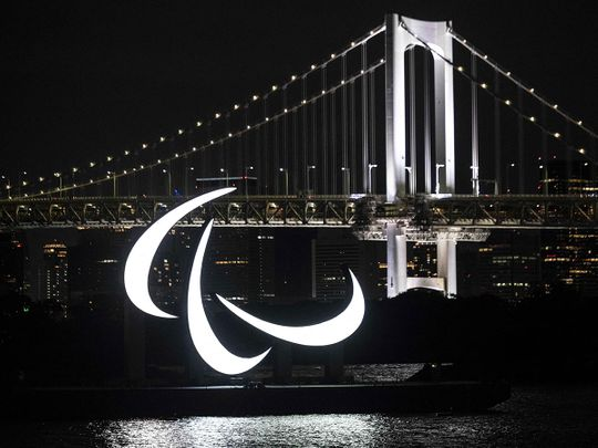 The Paralympics emblem lit up with the Rainbow bridge in the background, on the Odaiba waterfront in Tokyo