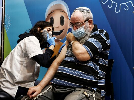 A man receives his third dose of the COVID-19 vaccine in Jerusalem.