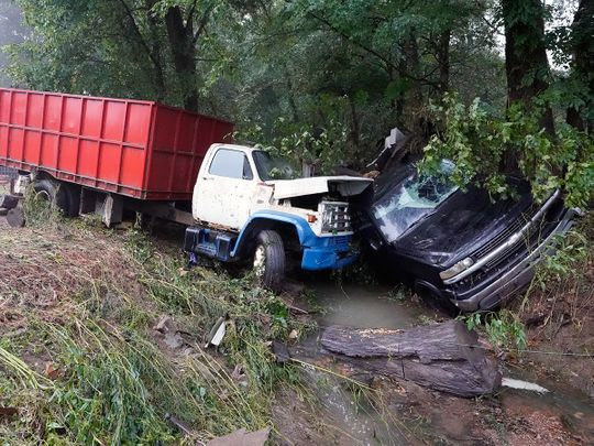 A truck and a car sit in a creek, after they were washed away the day before in McEwen, Tennessee.