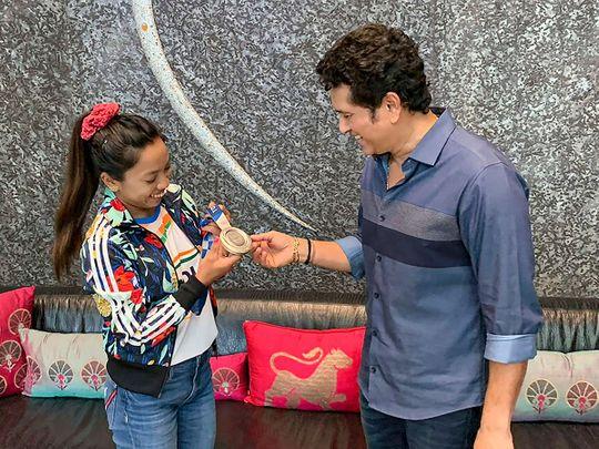 Tokyo Olympics silver medallist weightlifter Saikhom Mirabai Chanu shows her medal to cricket legend Sachin Tendulkar