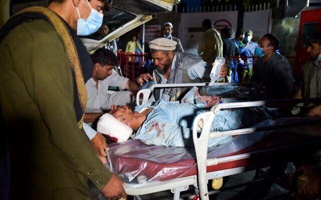 Medics and hospital staff bring an injured man