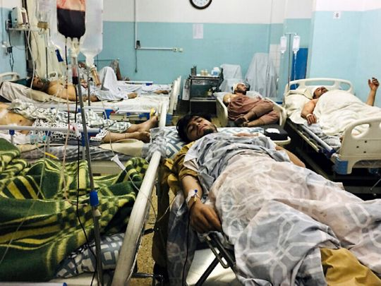 Wounded Afghans lie on a bed at a hospital after a deadly explosion