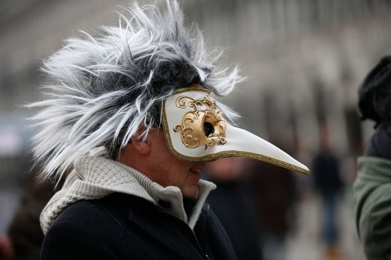 In this Jan. 24, 2016 file photo, a man wears a pest doctor mask in St. Mark's Square in Venice, Italy. This carnival mask derives from 16th century doctors wearing beak-nosed masks filled with aromatic herbs to cleanse the air they breathed when treating the sick