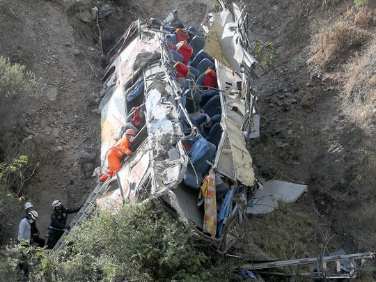 Rescue workers check a bus after it crashed, in Matucana, Peru, on August 31, 2021.