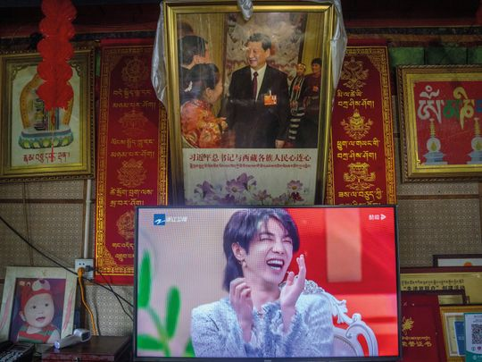In this June 4, 2021, file photo, a television shows a broadcast of a Chinese talk show program as it sits beneath a photo of Chinese President Xi Jinping in a home converted into a tourist homestay in Zhaxigang village near Nyingchi in western China's Tibet Autonomous Region.