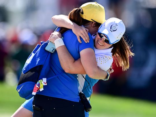 Europe's Leona Maguire celebrates with her sister Lisa after defeating United States' Jennifer Kupcho on the 15th hole during the singles matches at the Solheim Cup