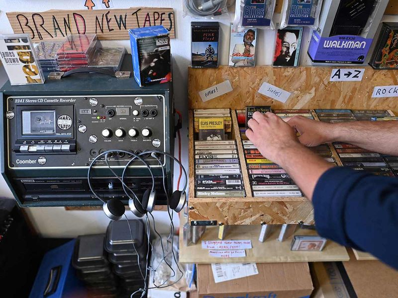 Giorgio Carbone, co-founder of Mars Tapes looks at cassettes in his shop in Manchester.