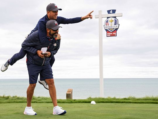Team US star Justin Thomas jumps on caddie Michael Greller during practice for the Ryder Cup