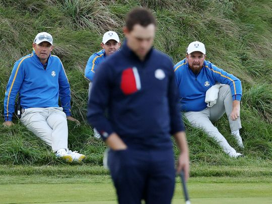 Captain Padraig Harrington of Team Europe, Rory McIlroy and Shane Lowry look on as Patrick Cantlay of Team US putts on the 18th green