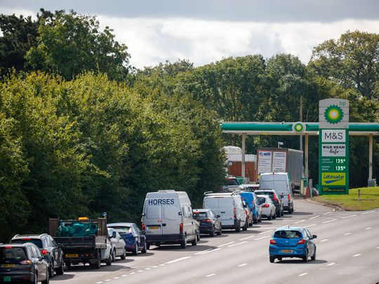 Cars queue up to use the fuel pumps at BP Plc petrol station near Guildford