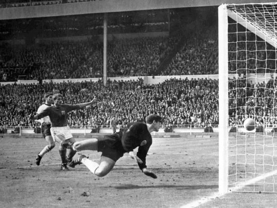 England's Roger Hunt raises his arms as Geoff Hurst scores England's third goal against West Germany