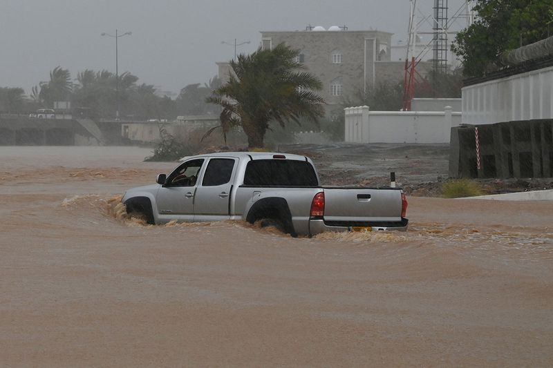 A SUV makes it way through a flooded street as Cyclone Shaheen makes landfall in Muscat Oman.