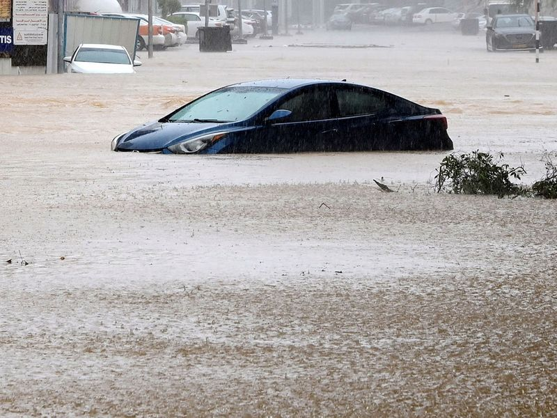 A car is partially submerged on a flooded street as Cyclone Shaheen makes landfall in Muscat Oman, October 3, 2021.