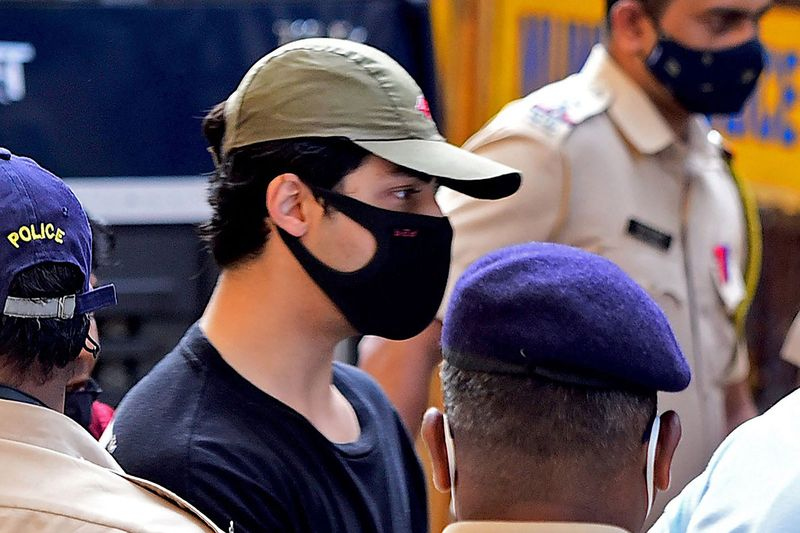 Bollywood actor Shah Rukh Khan's son Aryan Khan is being escorted by law enforcement officials outside the Narcotics Control Bureau (NCB) office after he was allegedly brought in for questioning along with others following a raid at a party on a cruise ship, in Mumbai on October 3, 2021.
