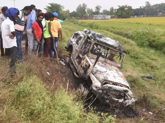 People take a look at the vehicle which was destroyed in violence during farmers' protest at Lakhimpur Kheri district in UP, India