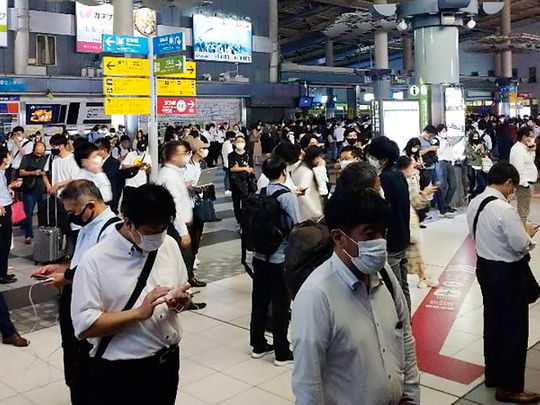 Passengers are seen outside the entrance of JR Shinagawa station as the railway company makes safety check following an earthquake, in Tokyo, on Thursday, October 7, 2021.