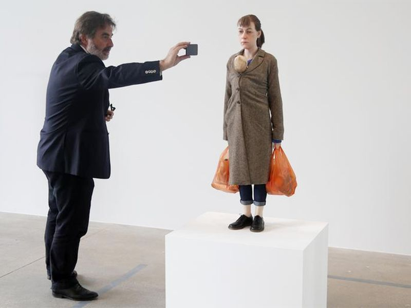 A visitor takes a picture of a sculpture entitled
