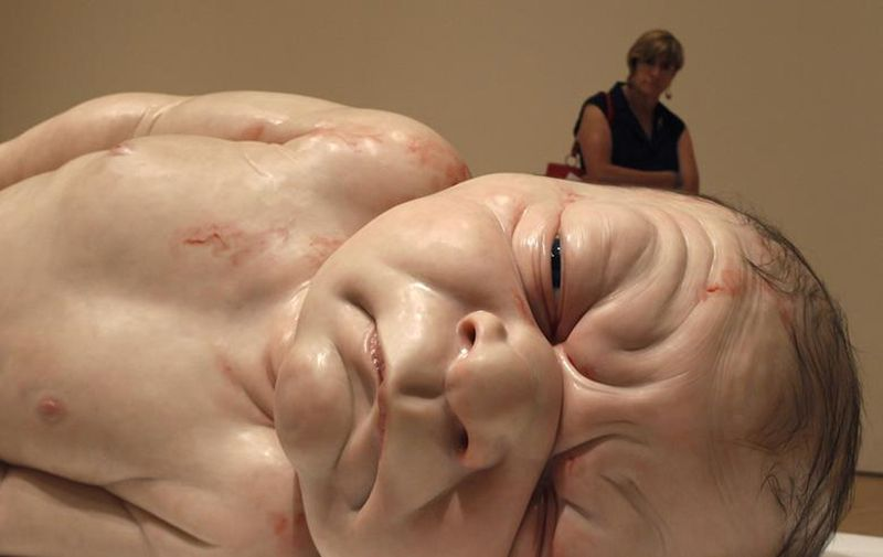 A woman looks at a sculpture entitled