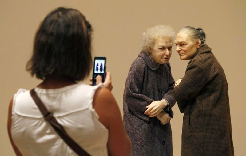 A woman takes a photo of a sculpture titled