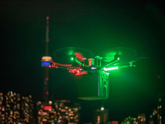 Unither Bioelectronique's drone transporting a pair of donor lungs, high above Toronto traffic at night.  A