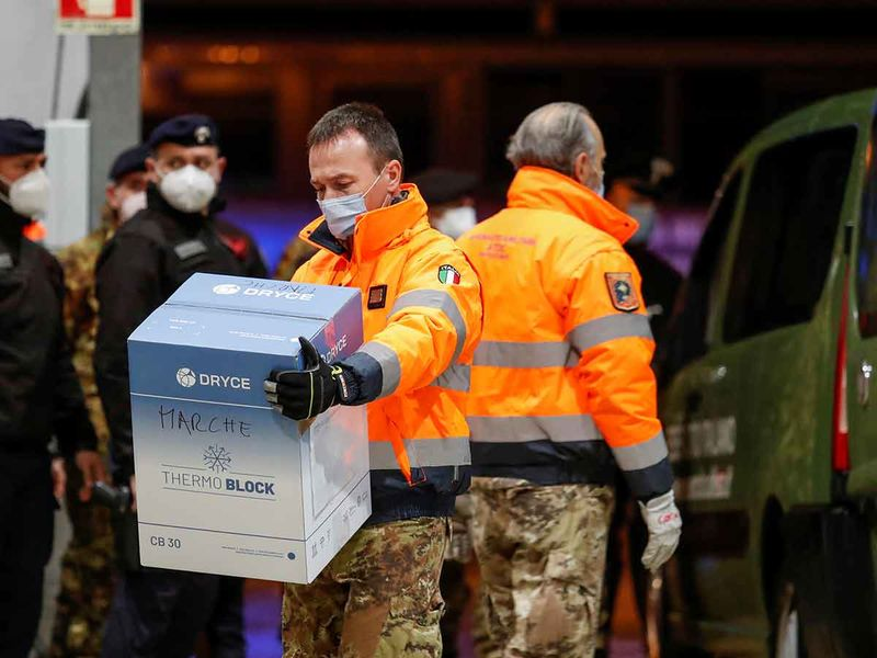 A member of the military carries a box containing the Pfizer-BioNTech coronavirus disease (COVID-19) vaccine to hangar at Pratica di Mare Air Base near Rome, Italy, December 26, 2020.