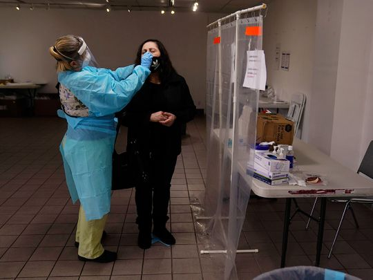 A nurse collects a nasal swab