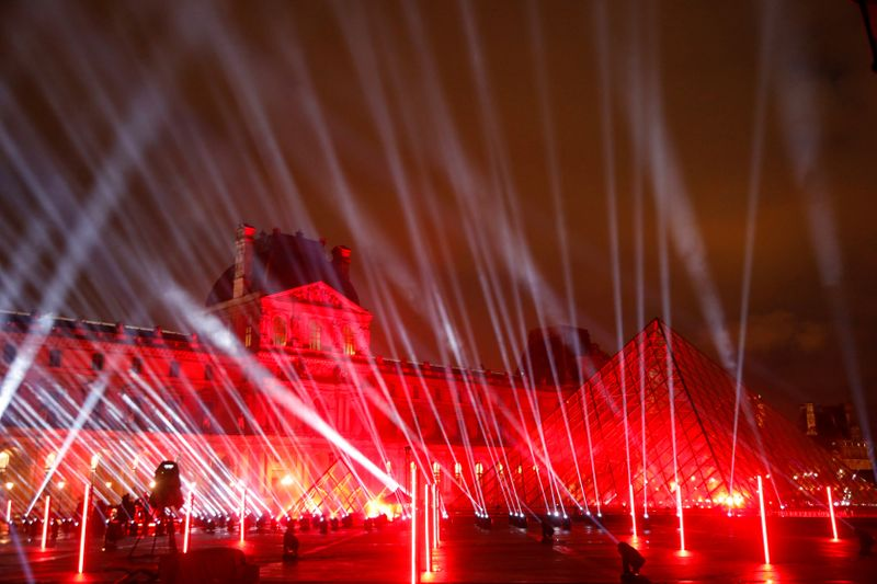 The Louvre Pyramid designed by Chinese-born U.S. architect leoh Ming Pei is illuminated before the ' United at Home ' fundraising live concert by French DJ David Guetta for New Year's eve, in Paris, France, December 29, 2020. Picture taken December 29, 2020. REUTERS/Charles Platiau