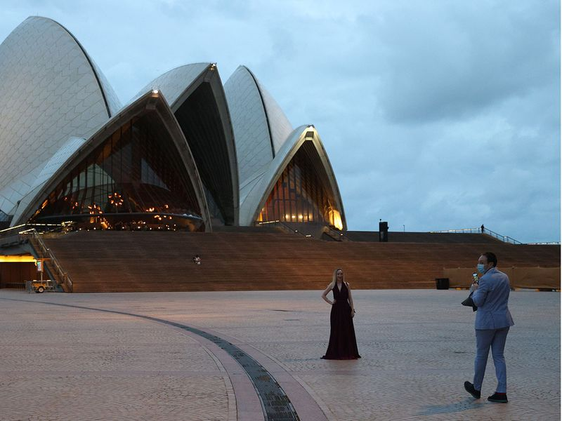 A woman poses for a photo in front of the Sydney Opera House as a small number of people begin celebrating New Year's Eve at the Sydney Harbour waterfront amidst tightened COVID-19 prevention regulations in Sydney, Australia.