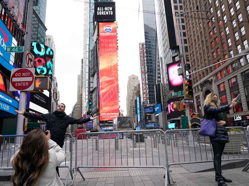 People pose for photographs while wearing protective masks during the coronavirus pandemic in Times Square Thursday, Dec. 31, 2020, in New York.